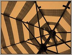 Provides shade (Bob R.L. Evans) Tags: parasol umbrella sepiatone shade unusual triangles summer beach abstract