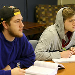 Two students listening intently as they take notes in class.
