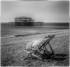 Gone (ArtfulAl) Tags: brighton deckchair grain mono blackandwhite lumix lx5 sea beach pier niksilverefexpro2 square