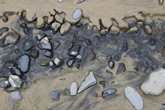 Tidal water run-off washes away parts of sand around rocks (nikname) Tags: oregonbeaches oregoncoast beachtextures sandytextures sanddesigns rocks rocktextures rockdesign beachrocks