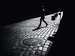 crossing the street (Sandy...J) Tags: light shadow darkness noir walk man blackwhite monochrom streetphotography silhouette cobblestones olympus city