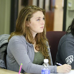 A student taking notes as she listens in class.