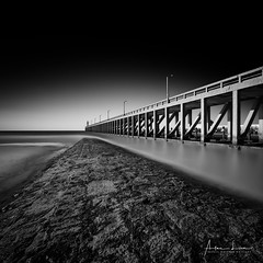 Pier And Breakwater In BW (Alec Lux) Tags: bw beach belgium blackandwhite blackandwhitephotography blankenberge landscape landscapephotography lighthouse long exposure longexposure longexposurephotography nature naturephotography ocean pier pontoon scenic sea seascape seascapephotography sky water waves vlaanderen be