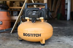 yellow Bostitch air compressor in a woodshop (yourbestdigs) Tags: air compressors compressor tire tires wood working woodworking pneumatic tools tool garage carpentry woodshop shop concrete work bench workbench airtools valves guages electric electronics valve wheels baseboards diy household housework house fix fixing building build do it yourself home project projects spray sprayer