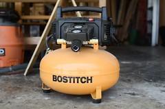 yellow Bostitch air compressor in a woodshop