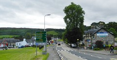 Welcome to Drumnadrochit, June 2017 (allanmaciver) Tags: drumnadrochit great glen signpost places names tourist centre loch ness entrance exit trees local newsagent post office coffee tea bed breakfast eat out pelican crossing allanmaciver village highlands highland