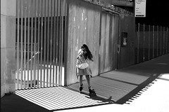In the shade of bars (pascalcolin1) Tags: paris13 girl fille rollers ombres shadows barriere barrier barreaux bars light lumière soleil sun photoderue streetview urbanarte noiretblanc blackandwhite photopascalcolin