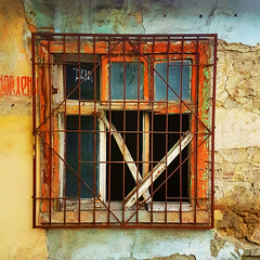 Home security (Arni J.M.) Tags: window metalwindowbars homesecurity square glass broken frame decay abandoned discoloured wall chisinau moldova