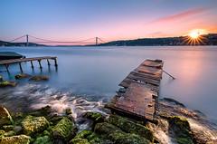 The Bosphorus Bridge (Guner Gulyesil) Tags: rock güneş bridge sunstar city boğaz turkey sea rengarenk deniz fotoğraf algae fotoğrafçılı wave türkiye yosun köprü uzunpozlama bogazici şehir bosphorus sunrise sunset fotoğrafyarışması gunergulyesil istanbbulbüyükşehirbelediyesi çengelköy longexposure cityscape ödül istanbul boğaziçi rocks silüet sun türk urban silhouette construction colorful cloud boğaziçiköprüsü moss iskele green boğazköprüsü cengelkoy sunflare dalga