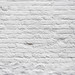 Brick wall with a layer of white paint