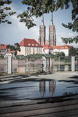 Reflection in the mirror (Soren Wolf) Tags: wrocław wroclaw poland cathedral st john baptist water river bench mirror towers sky clouds cloud tower puddle nikon d7100