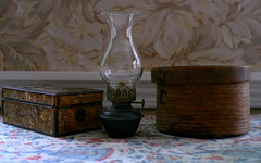 Old things L3184186 (LarryJ47) Tags: leica leicax1 old antique antiquity table tablecloth lamp kerosene box wooden boxes sidelight reflection mood atmosphere