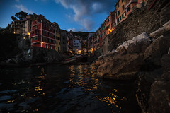 an evening in Riomaggiore (levibohnacker) Tags: riomaggiore marina port harbour cinque terre 5 5terre italy la spezia landscape nature architecture house houses village settlement city night blue hour clouds cloud sky water ocean wave waves mediterranean ligurian sea coast cliff cliffs clourful longtime exposure nightlife colours summer refletion orange light travel travelling