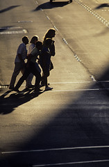 """Silhouetted family crossing street toward sunset along """"The Ave"""" in the University District Seattle, Washington State USA (Jim Corwin's PhotoStream) Tags: silhouetted silouettes man male boy youth youthful summer leisure leisureactivity sunset urban urbanscene downtown street streetscene mystery family quiet photography vertical isolation single city cities dark mysterious shadowyfigure intersection universitydistrict seattle lifestyle womansilhouetted womanwomen crosswalk cars"""