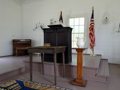 Harmony Hall Chapel Stage. (dccradio) Tags: whiteoak nc northcarolina bladencounty flag americanflag podium stage steps stairs pulpit organ window globe lantern wallmountedlantern lamp oillantern oillamp whitewall wood wooden churchorgan rug carpet table communiontable basket christianflag indoors interior inside churchstage harmonyhallchapel harmonyhallplantation plantation harmonyhall history historical historicalsite livinghistory nikon coolpix l340 pitcher waterpitcher candles candle candleabra candelabrum candletree