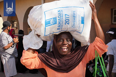 A woman smiling as she carries a food parcel given in the holy month of Ramadan in Zimbabwe.