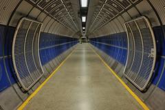 Otherworld (Douguerreotype) Tags: uk gb britain british england london city urban tunnel underground tube metro subway blue yellow gate metal architecture empty symmetry futuristic scifi