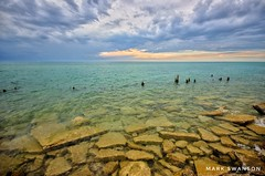 Stones and Pilings (mswan777) Tags: sunset cloud sky shore coast lake michigan seascape stevensville summer evening rock water waves piling wood nikon d5100 sigma 1020mm scenic glow landscape