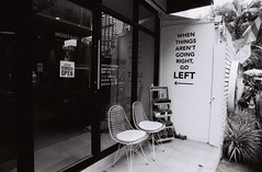 Go Left - Thong Lo, Bangkok (35mm) (jcbkk1956) Tags: film 35mm analog nikon nikonf manualfocus manualexposure ilford ilfordpan100 street bangkok thailand thonglo sign 20mmf4 nikkor cafe coffeeshop worldtrekker chairs