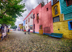 Colorful La Boca in Buenos Aires, Argentina (` Toshio ') Tags: toshio laboca argentina buenosaires barrio neighborhood colorful architecture street tree southamerica road city fujixe2 xe2 man dog art bench cloudy