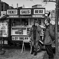 Mind your head (John Riper) Tags: johnriper street photography straatfotografie square bw black white zwartwit mono monochrome candid john riper canon 6d 24105 l liverpool england uk ticket booth sales tours mind head man woman stand stall car tuktuk port harbour harbor