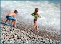 Strandspiel (sinepo) Tags: france meer starnd steine kinder junge mädchen badehose unscharf bikini schwimmring