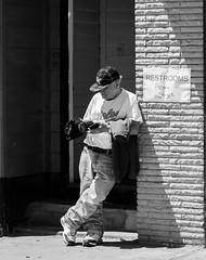 Across From The Restrooms (John Kocijanski) Tags: sign people man hats blackandwhite streetphotography streetcandid canon24105mmf4l canon5dmkii