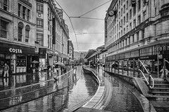 Oh look, it's raining (tootdood) Tags: canon70d blackandwhite streetcandid market street manchester wet weather rain umbrella brolly sheen oh look its raining metro stop station metrolink stormy sky black clouds