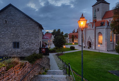 Visby Cathedral Park III (henriksundholm.com) Tags: city urban oldtown gamlastan church cathedral architecture dusk bluehour cobblestone shadows grass lawn houses paths roads street balcony lamp light windows trees bench stairs steps summer hdr scenery gothic medieval visby gotland island sverige sweden nikon