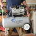 woodworker holding silver air compressor in wood shop