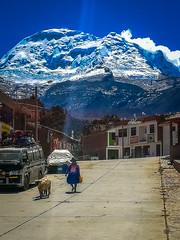 A woman walking her animals with Mt. Huascaran in the background.