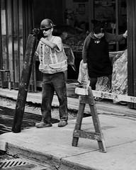 Open for Business  /  Ouvert (H - - J) Tags: street sidewalk construction worker hardhat woman storeowner barrier grate pipe outdoor safetyvest store shop vegetables veggies fruit shelf pavement door slidingdoor blackandwhite monochrome monotone noiretblanc hole jeans safetyboots sunglasses gloves workgloves apron