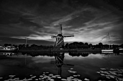 De Hommel B/W (l.cutolo) Tags: tlp water clouds netherlands cloudysky boats reflections nightspot dehommel river night worldtrekker nightshorter flickr windmill aperture molen dusk lights a7ii sonyfe2470mmf40zaoss