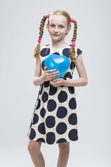 Portrait of Funny Caucasian Blond Girl With Pigtails Posing in Polka Dot Dress Against White. Holding Blue Air Balloon. (DmitryMorgan) Tags: 1 710years adorable airballoon baby beautiful blond blowup caucasian cheerful child childhood daughter dress european expression female fun girl heartformed holding human inflate joy kid little love model mood one pigtails polkadot portrait positive preschooler school schoolgirl small smile smiling straw studio white young