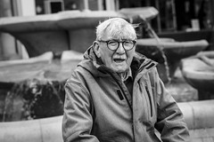 Fountain of Youth (Leanne Boulton) Tags: urban street candid portrait portraiture streetphotography candidstreetphotography candidportrait streetportrait eyecontact candideyecontact streetlife old elderly man male aged face facial expression eyes look emotion feeling mood atmosphere fountain dutchangle tone texture detail depthoffield bokeh naturallight outdoor light shade shadow city scene town human life living humanity society culture people canon canon5d 5dmkiii 70mm character ef2470mmf28liiusm black white blackwhite bw mono blackandwhite uk england warwickshire nuneaton