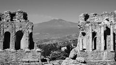 Taormina Greek Theater and Mount Etna. (Flyingpast) Tags: sicily italy greektheater mountetna ruin historic tour unesco vacation volcano landscape taormina blackandwhite dramatic setting
