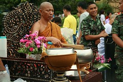 an important monk blessing people (he dips the whisk in water and flings the water at people) (the foreign photographer - ฝรั่งถ่) Tags: important monk chair whisk blessing people bowls flowers wat prasit mahathat bangkhen bangkok thailand canon