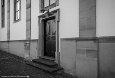 The side entrance of the church. (andreasheinrich) Tags: architecture church door afternoon june blackandwhite blackandwhitephotos warm overcast germany badenwürttemberg neckarsulm dahenfeld deutschland architektur kirche tür nachmittag juni schwarzweis bewölkt nikond7000