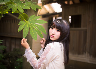 Portrait of young woman touching big green leaf in old Japanese garden