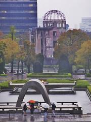 Hiroshima VIII (Douguerreotype) Tags: japan hiroshima rain weather people street umbrella war memorial atom bomb dome arch trees remembrance abomb