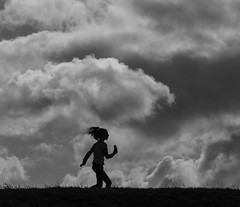 windy day (Georgie Pauwels) Tags: bnw sky girl windy clouds wind street blackandwhite candid streetphotography moment olympus