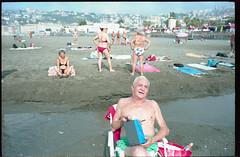 (On The Same Wavelength) (Robbie McIntosh) Tags: leicamp leica mp rangefinder streetphotography 35mm film pellicola analog analogue negative leicam elmarit analogico leicaelmarit28mmf28iii elmarit28mmf28iii dyi selfdeveloped filmisnotdead autaut candid bellinifotoc41 kodakportra160 kodakportra portra kodak beach tan seaside bathers strangers swimsuit lidomappatella mappatellabeach singer man radio belly eyecontact smile