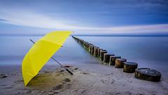 There is no bad weather. ([-ChristiaN-]) Tags: umbrella rain weather groynes sea ocean silence calm blue yellow beach longexposure langzeitbelichtung regenschirm weer tempo vetero tiempo temps guardachuva ombrelo paraguas ombrello seafront regen tokinaatx116prodx