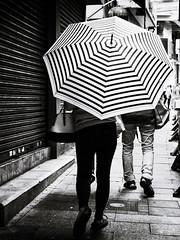Hypnotic Umbrella (Feldore) Tags: umbrella hong kong street hongkong woman holding pattern lines lined hypnotic geometric candid feldore mchugh em1 olympus 1240mm