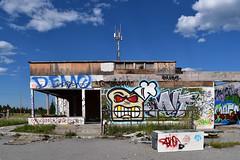 Abandoned garage between Canmore and Banff (Jane Olsen) Tags: graffiti colorfuldrawings art urban outdoor alberta cupcake clouds sky ground grass dirt debris cardboard