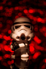 Click the star or I'll blast ya...... (The Manic Macrographer) Tags: stormtrooper starwars bokeh dof figurine toy reflection tabletopphotography indoors torchlight tripod canon7d canon60mmmacrousm blaster redbackground red