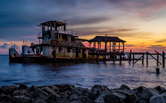 Stranded in Time (fuzzy_dunlop_nola) Tags: fuji 35mm mirrorless light evening scenic ship stranded decay xt2 fujixt2 colors madisonville waterscape view vantage sunlight southlouisiana colorful color vivid lakefront shore provia shoreline louisiana old rustic cloudy tug tugboat lakepontchartrain lake xf35mmf14r fujinon seascape scape rust bluehour thebluehour lakeshore waterfront madisonvillelouisiana