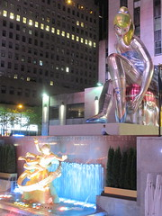 Seated Ballerina Mylar Balloon at Night 6234 (Brechtbug) Tags: seated ballerina mylar balloon night art sculpture by jeff koons 2017 rockefeller center nyc 30 rock new york city standing up above ice rink gold prometheus statue paul manship giant decoration ornaments 05202017 nights nite nites lights lites light oversize load ornament summer spring kids toy kitsch 60s toys sculptures statues pretty evening lobby plaza plant plants plastic artist