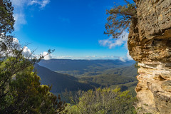 Beneath the Three Sisters (Anthony Kernich Photo) Tags: threesisters rock cliff formation view nsw australia newsouthwales panorama pano panoramic olympus photo photography travel scene scenic amazing wow beautiful attraction bluemountains katoomba mountain park icon famous lookout sydney stunning trees rocks sky olympusem10 olympusomd leura green landscape rayleighscattering natural nature breathtaking best flickr nationalpark morning