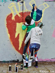 Graffiti artist at work... (Akbar Simonse) Tags: denhaag thehague agga lahaye sgravenhage haag holland netherlands nederland graffiti artistatwork boy woman mother people candid streetphotography streetshot straatfotografie straatfoto color akbarsimonse spuitbussen spraycan